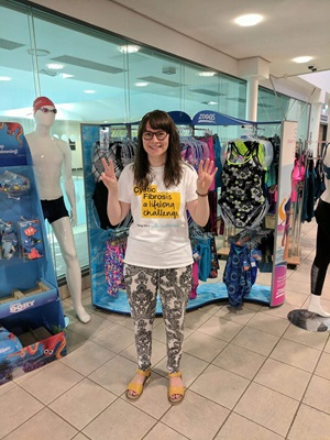 Woman wearing Cystic Fibrosis t-shirt smiles outside a shop front
