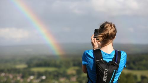 Young woman taking a photo of a rainbow and countryside