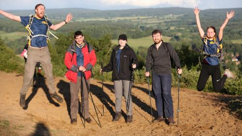 Five happy adults posing in walking gear with a countryside view behind them