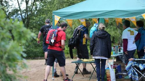 Adults in walking gear next to a gazebo with yellow bunting