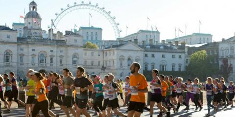 Large group of people running a marathon with the London Eye in the background