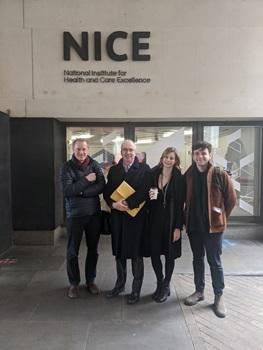 Four people standing outside of a building with NICE - National Institute for Health and Care Excellence - written on it