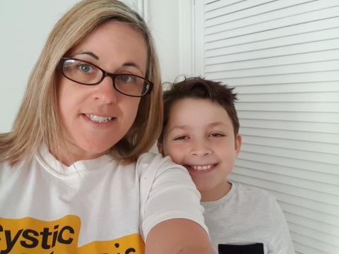 woman with blonde hair wearing glasses and white top with Cystic Fibrosis Trust logo, holding camera, small boy standing slightly behind with dark brown hair and white top, smiling