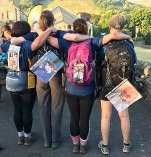 The backs four women wearing rucksacks with photos stuck to them