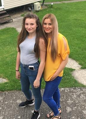 A young girl with brown hair, wearing a grey tank top, blue jeans and black trainers stands next to a woman with blonde hair wearing a yellow top, blue jeans and sandals. Both of them are smiling at the camera and they are standing outside in a garden.