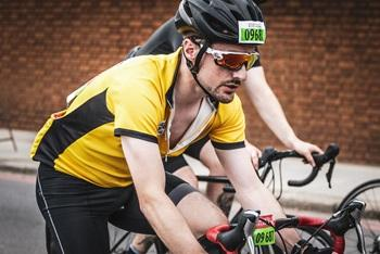 man on bike wearing yellow cycling jersey with black stripe, black helmet on red and black racing bike