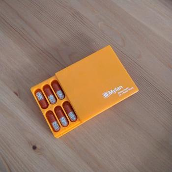 small orange box partly open with red and white medication inside in pill-shaped compartments