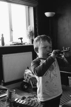 Black and white photo of young boy playing recorder