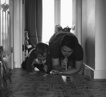black and white photo of mum and son kneeling down and blowing something along the floor with straws