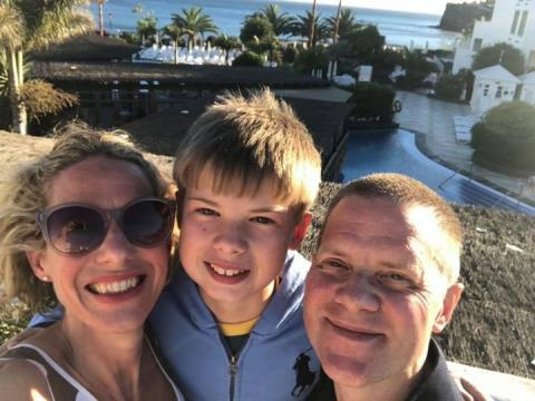 Tim with his wife Kate and their son Felix in front of a beach