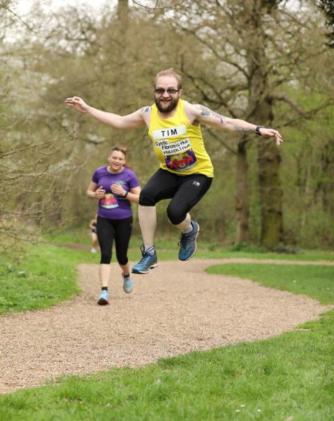 A man with a beard in a yellow running vest jumps into the air.