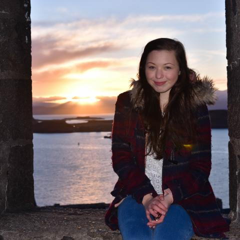 girl around 20's sitting on castle wall with sunset in background, long dark brown hair wearing maroon winter coat and blue jeans