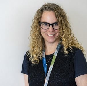 woman with blonde curly hair wearing glasses and a navy blue shirt with a lanyard
