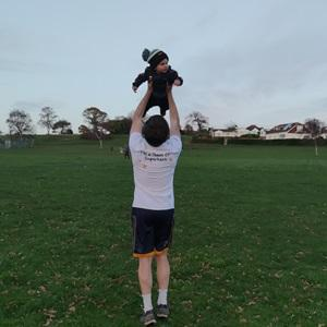 Man in activewear holding his baby aloft