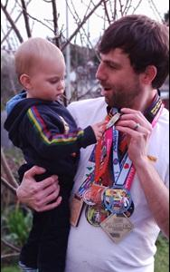 Man holding a baby who is looking at the medals around his neck